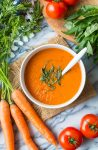 Low FODMAP Carrot Tomato Soup topped with fresh basil and surrounded by produce