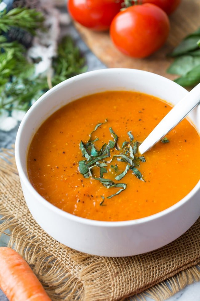 Low FODMAP Carrot Tomato Soup topped with fresh basil up close