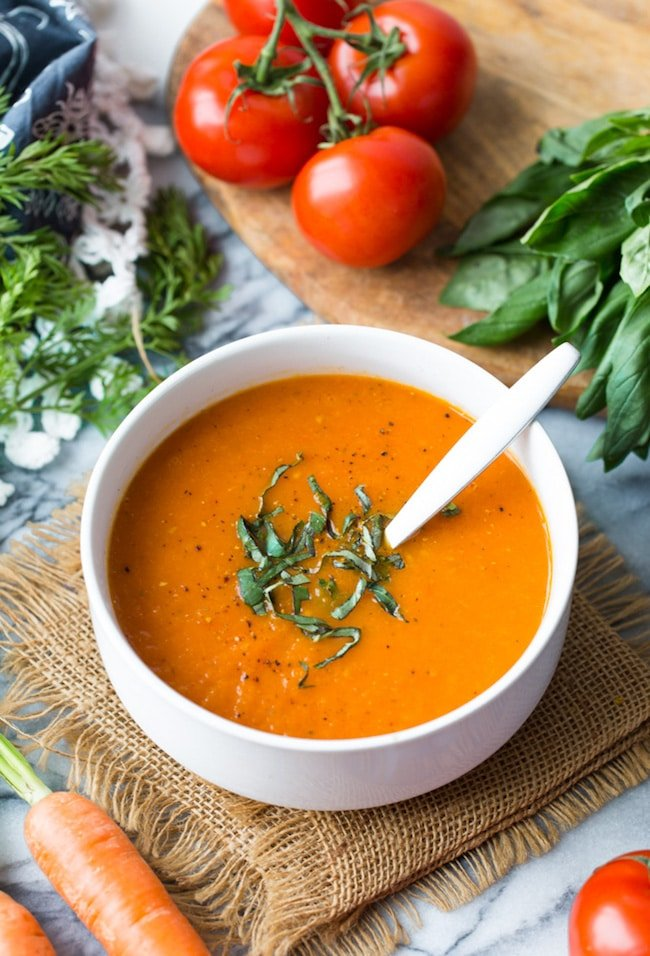 Low FODMAP Carrot Tomato Soup in a white bowl topped with fresh basil and surrounded by produce