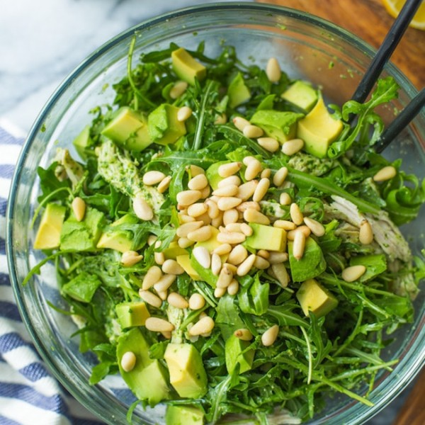 chicken pesto salad in a glass bowl topped with pine nuts