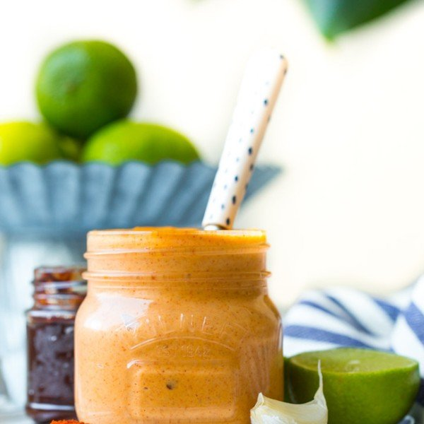 jar of chipotle mayo on a plate with garlic, lime and spices