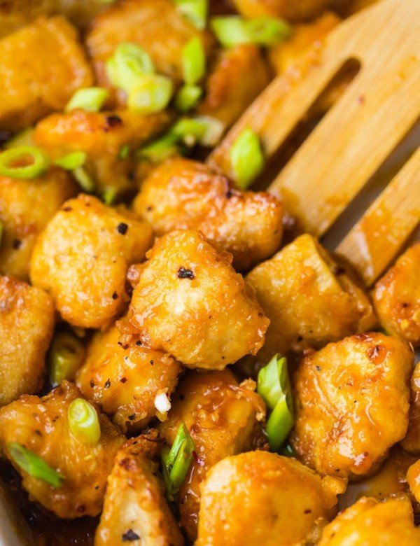 paleo fire cracker chicken topped with chopped spring onions stirred by a wooden spoon