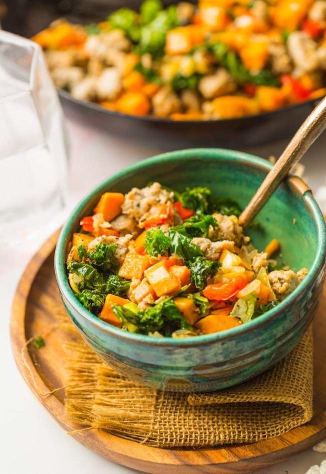 Sausage Kale Sweet Potato Hash in a green bowl with a fork