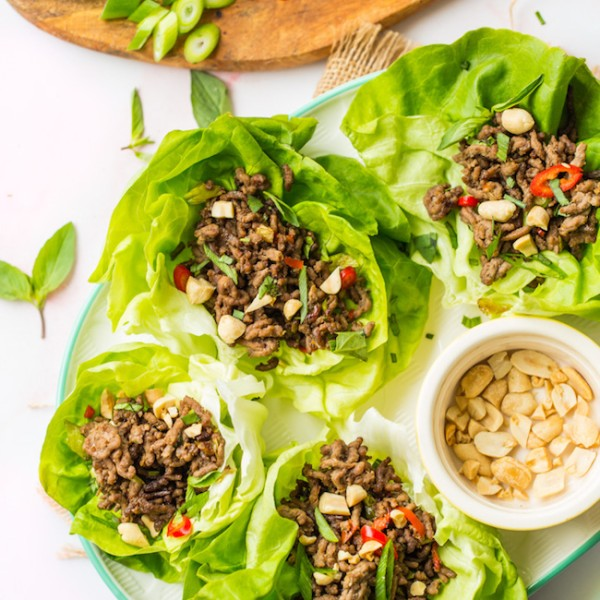 spicy beef lettuce wraps on a white serving platter topped with peanuts