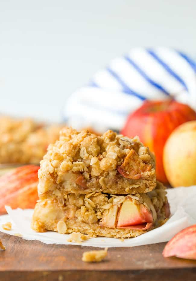 two apple crumble bars on a wooden cutting board