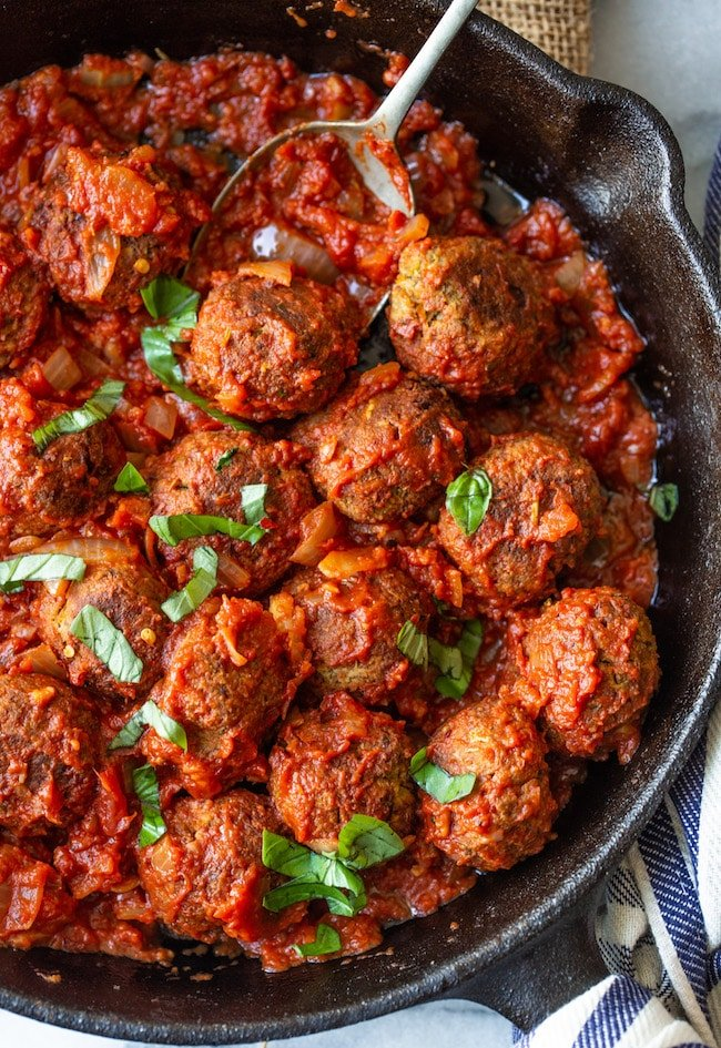 Vegan Lentil Meatballs up close in a cast iron skillet in marinara