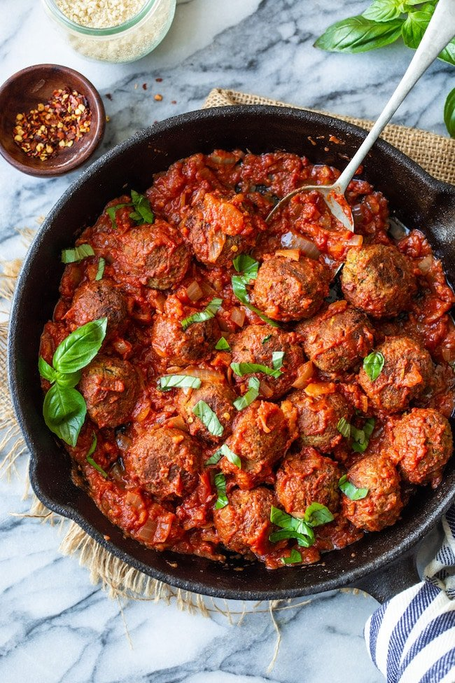 Vegan Lentil Meatballs in a cast iron skillet in marinara