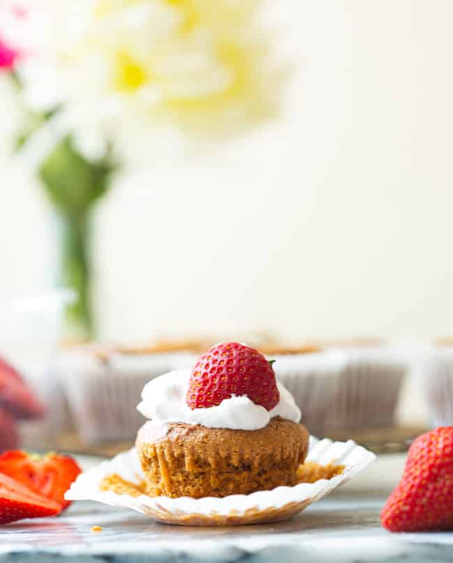 Paleo Vegan Cupcakes with whipped cream and a strawberry on top