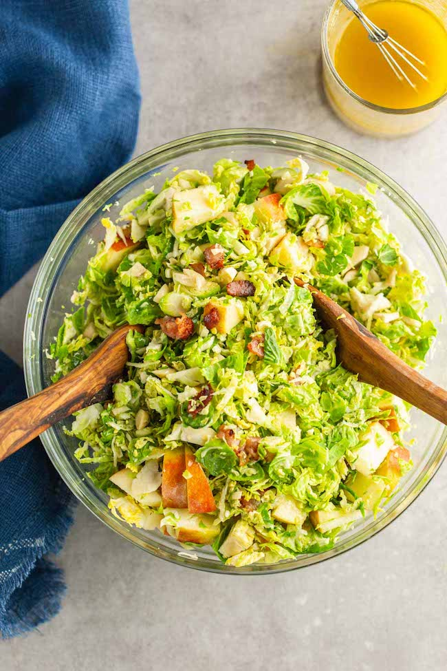Shaved Brussels Sprouts Salad with Apples & Honey Mustard Vinaigrette in a salad bowl with wooden tongs