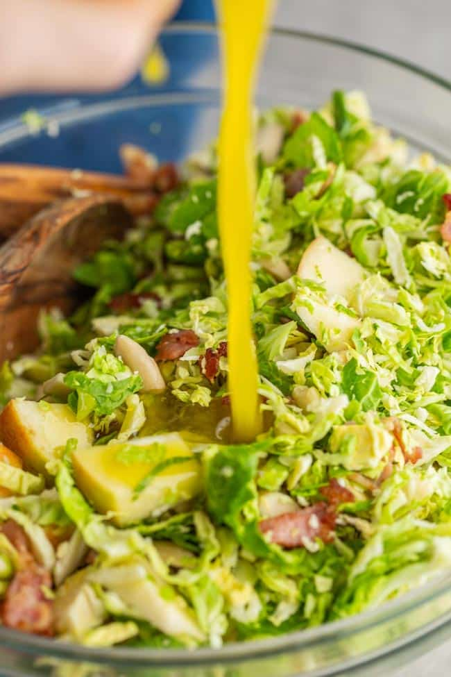 Honey Mustard Vinaigrette  pouring over Shaved Brussels Sprouts Salad with Apples