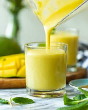 mango lassi pouring into a cup