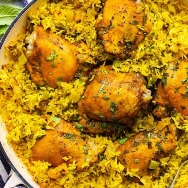 Herby Golden Baked Chicken and Rice in a casserole dish topped with topped herbs