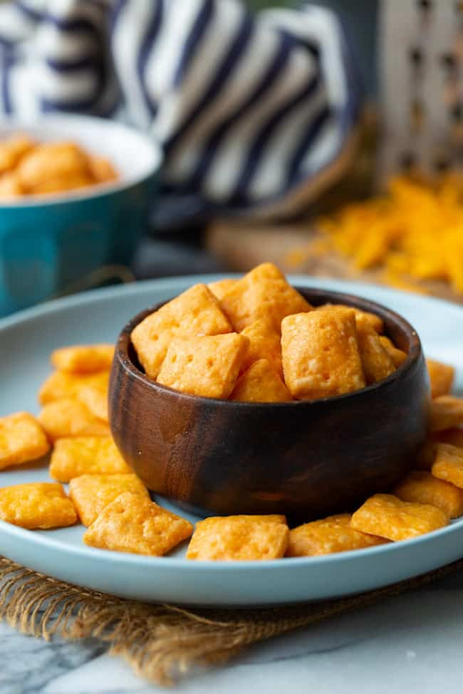 Cheesy Gluten Free Crackers in a small wooden bowl on a blue plate
