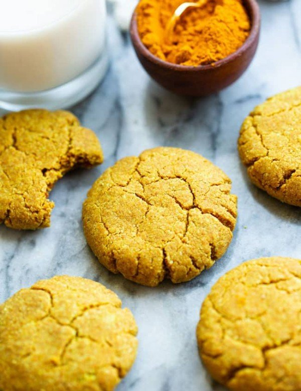 Golden Almond Cookies on a marble counter with powered turmeric