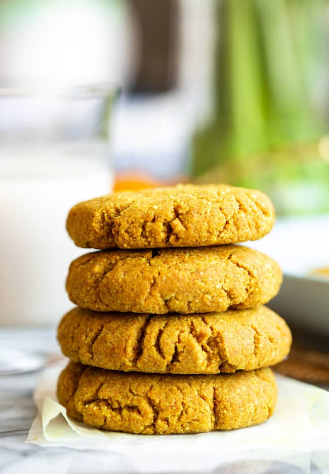stack of Golden Almond Cookies on a marble counter with powered turmeric