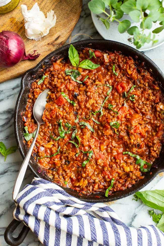 Lentil Bolognese in a cast iron skillet topped with basil