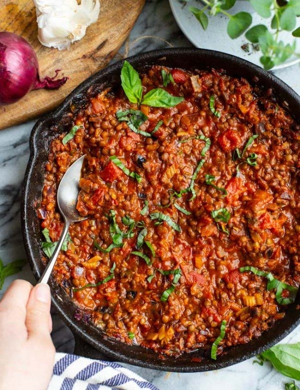 A hand scooping out a spoonful of Vegetarian Lentil Bolognese