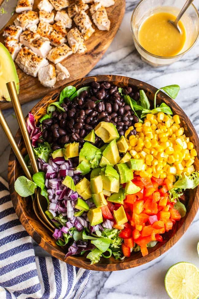 unmixed southwest chicken salad in a salad bowl with serving spoons