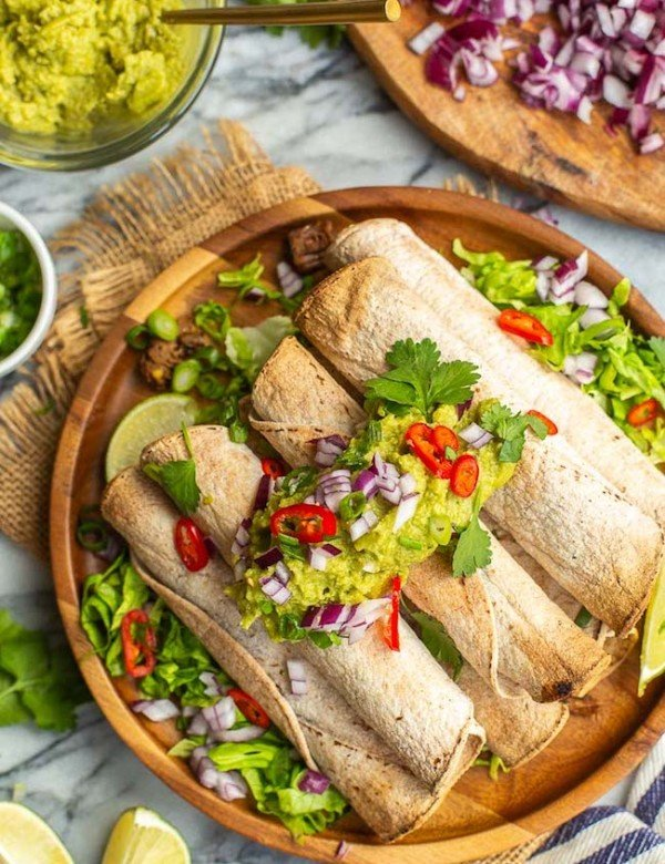 Jackfruit Carnitas Taquitos topped with guacamole and chilies