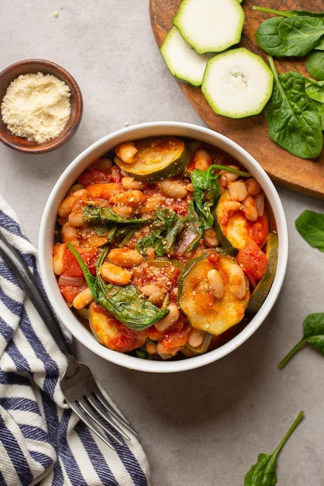 Zucchini and Cannellini Tomato Stew in a white bowl surrounded by spinach and zucchini