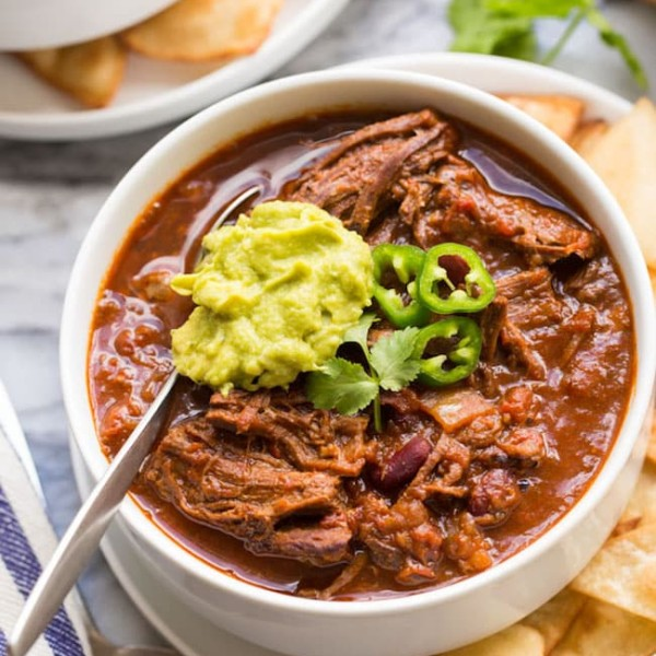 Instant-Pot-Chili-Con-Carne-with-Shredded-Beef in a white bowl topped with guacamole