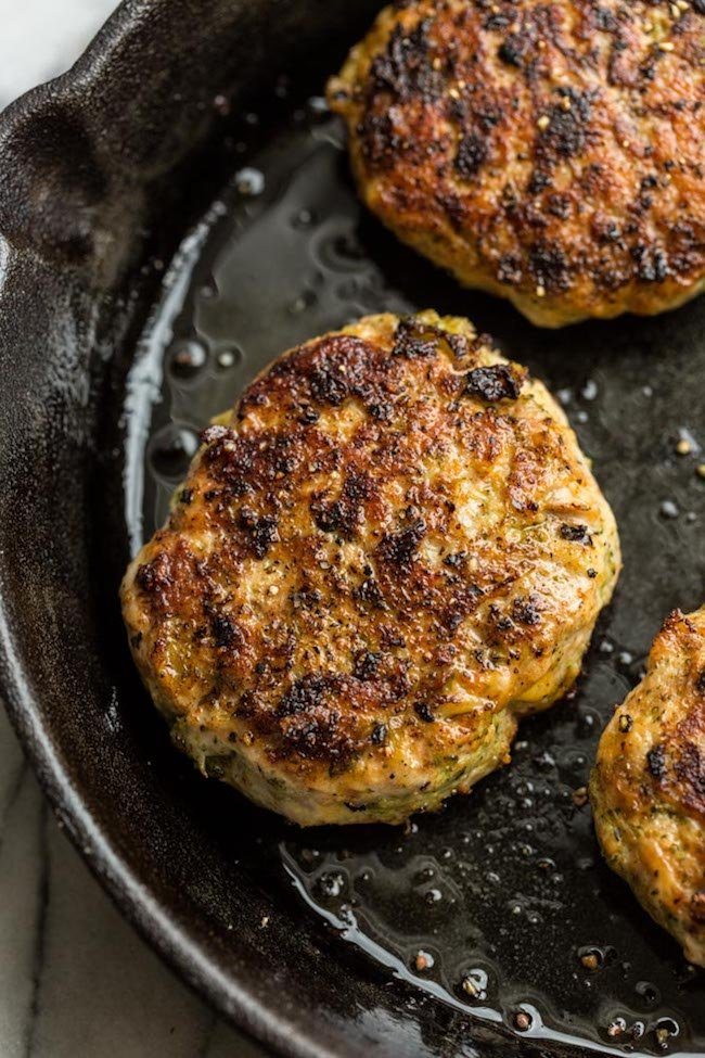 Broccoli Cheddar Chicken Burgers in a frying pan