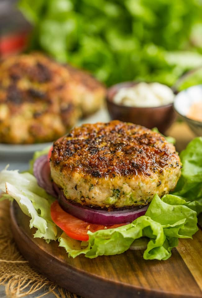 Broccoli Cheddar Chicken Burger on a lettuce leaf with onion & tomato