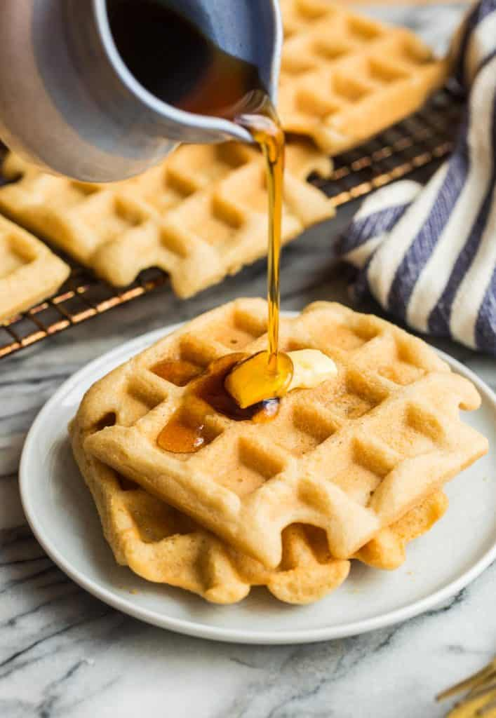 Almond Flour Waffles on a small plate with maple syrup pouring over the top