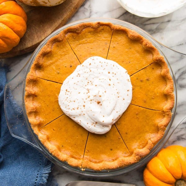 paleo pumpkin pie topped with coconut whipped cream surrounded by pumpkins
