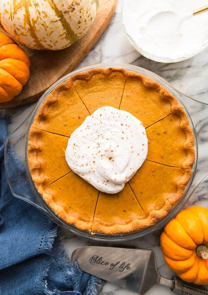 paleo-pumpkin-pie topped with coconut whipped cream and surrounded by pumpkins