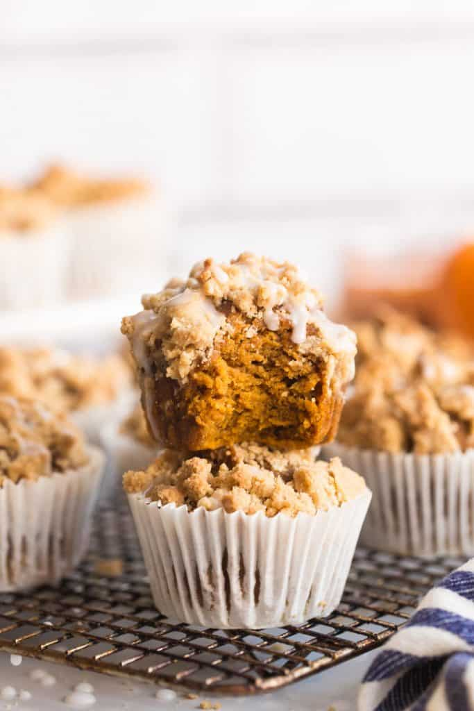 Pumpkin & Gingerbread Crumb Muffins stacked on a wire cooling rack