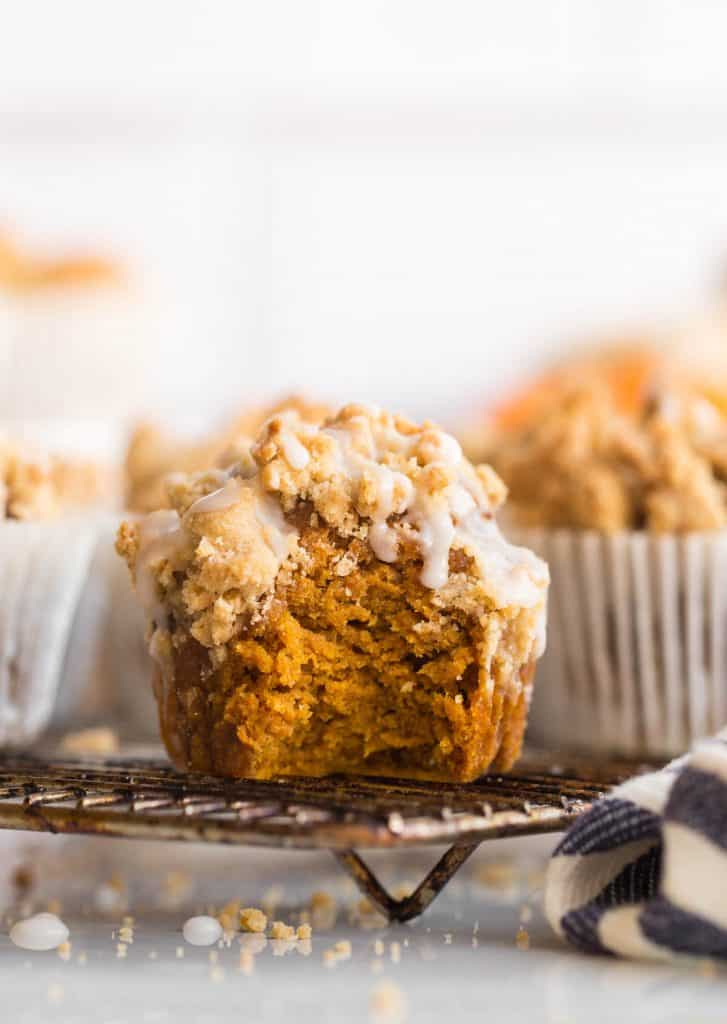 Pumpkin & Gingerbread Crumb Muffins with icing on a cooling rack