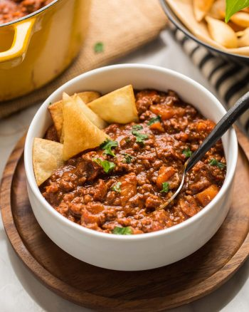 Smokey Sweet Potato Chocolate Chili in a white bowl with tortilla chips