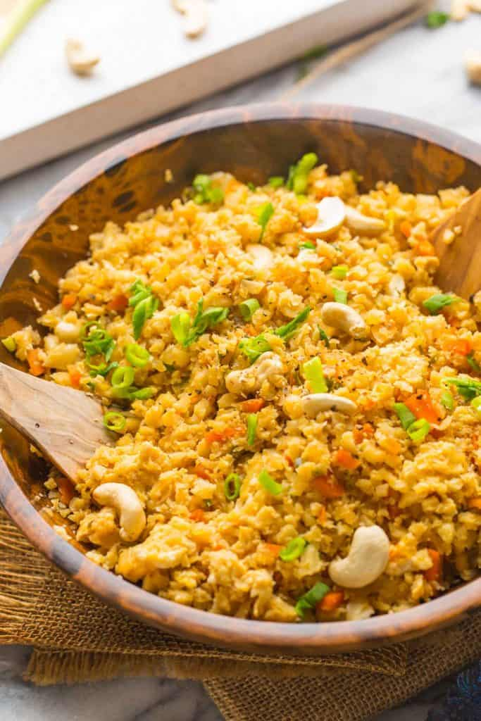 Cauliflower Egg Fried Rice topped with green onions in a wooden bowl