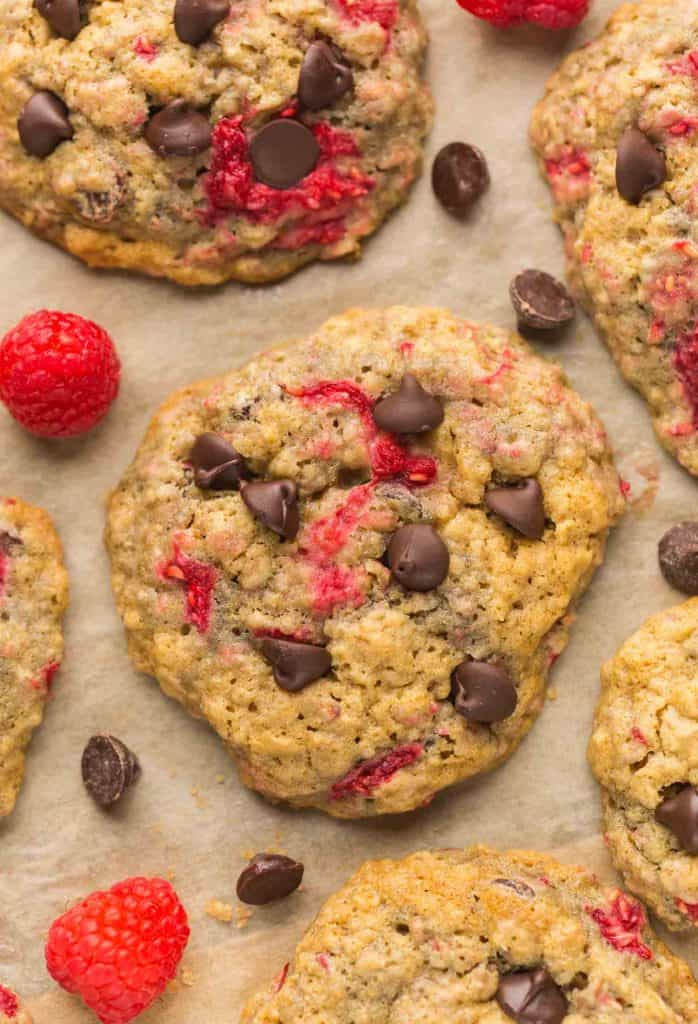 Oatmeal Raspberry Chocolate Chip Cookies on baking paper surrounded by raspberries and chocolate chips
