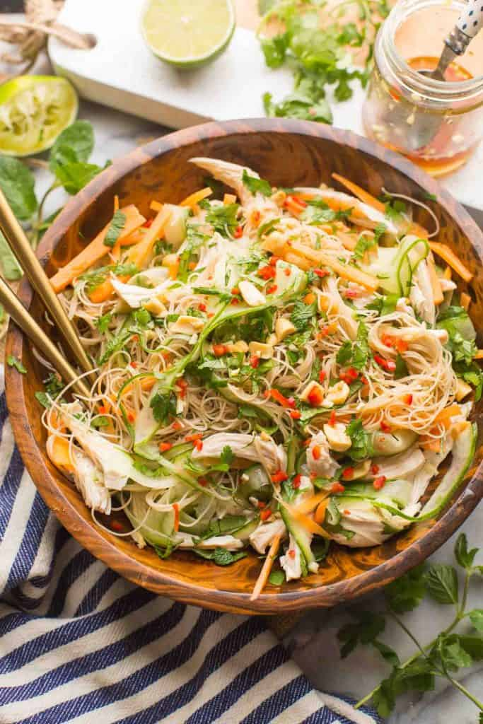 Vietnamese Chicken & Rice Noodle Salad in a salad bowl surrounded by fresh ingredients