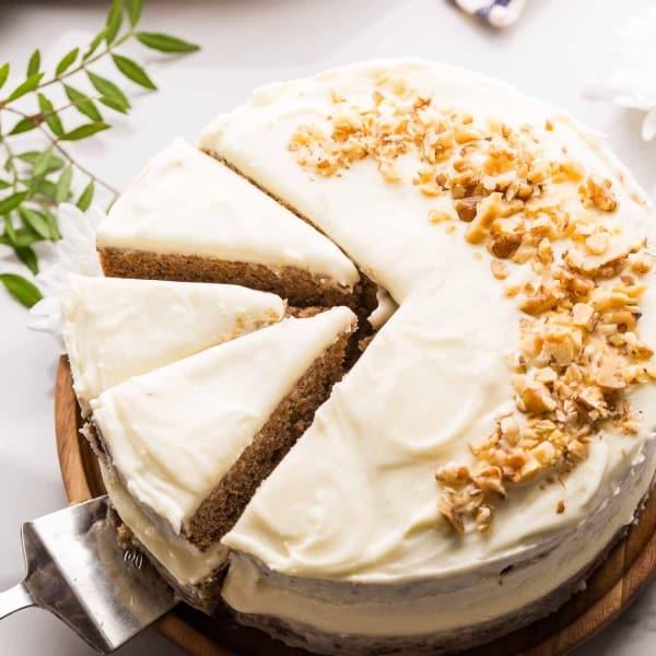 Gluten Free Carrot Cake topped with chopped walnuts on wooden platter