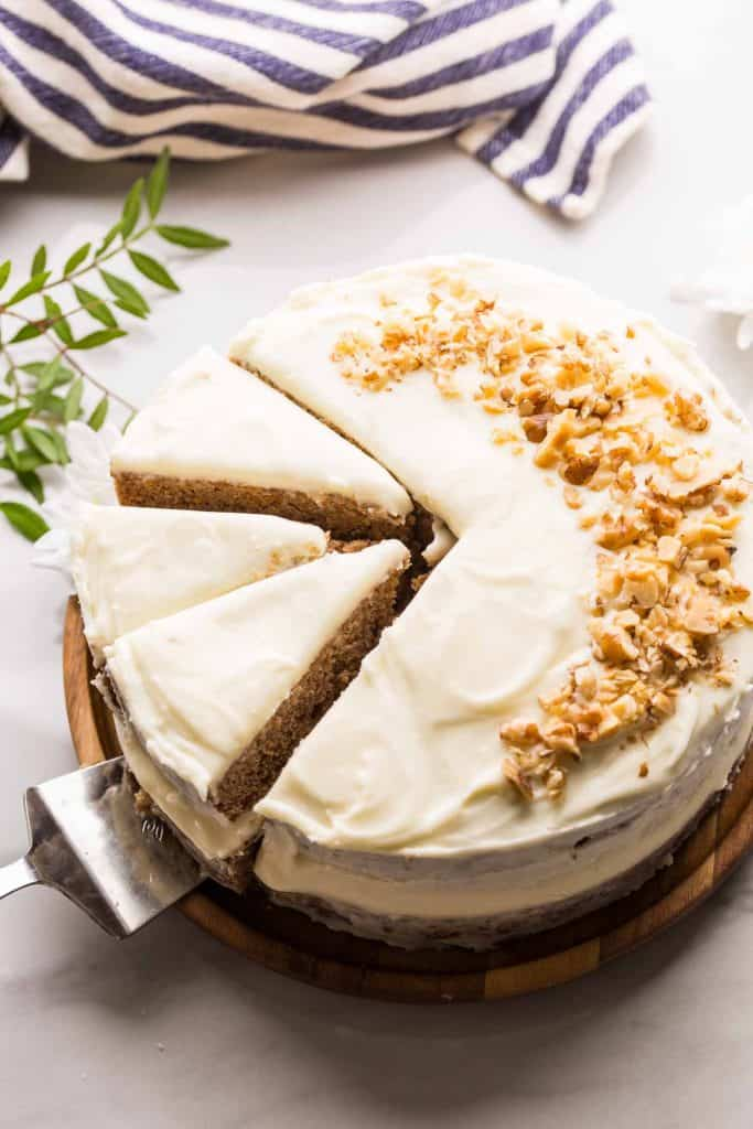 Gluten Free Carrot Cake topped with walnuts on a wooden platter