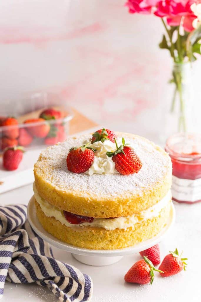 Gluten Free Victoria Sponge Cake on a cake platter topped with strawberries & whipped cream