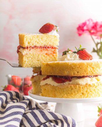 slice of Gluten Free Victoria Sponge Cake held up