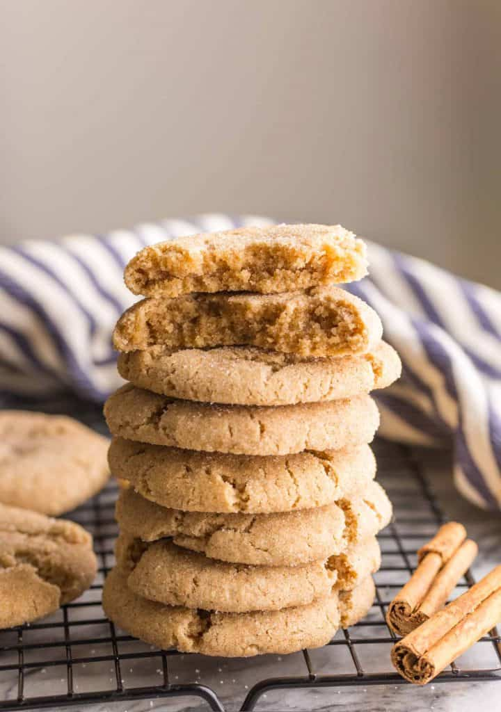 Almond Flour Snickerdoodles stacked on a wire cooling rack with one cookie cut in half