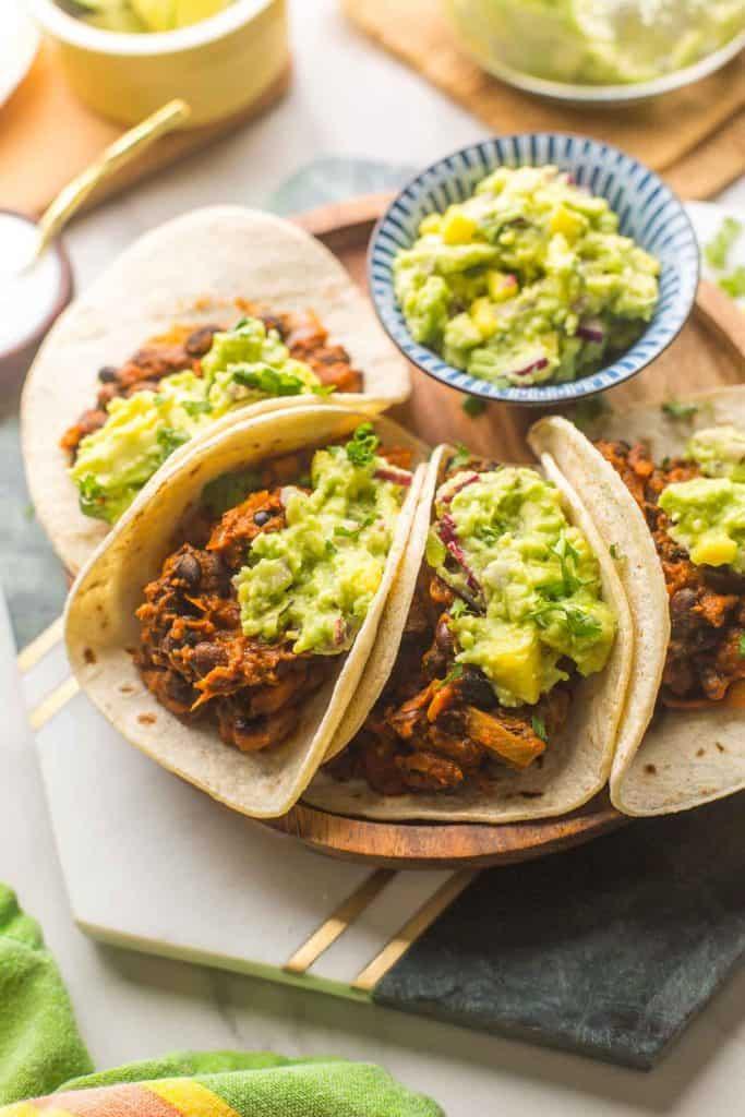 4 Vegan Black Bean Tacos with Mango Guacamole on top