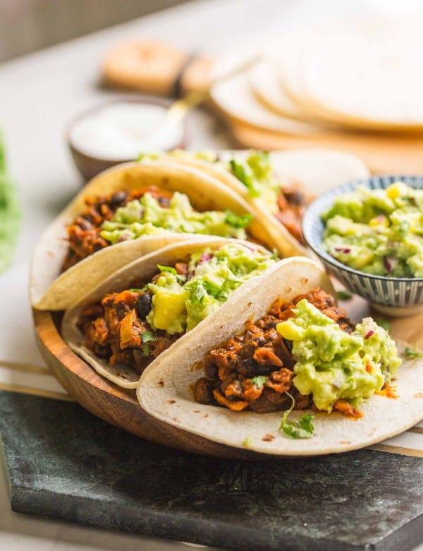 four Vegan Black Bean Tacos & Mango Guacamole on a plate