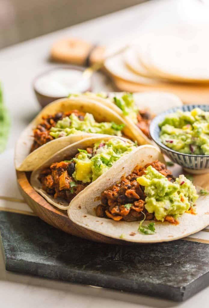 Vegan Black Bean Tacos & Mango Guacamole on a plate set on a marble slab