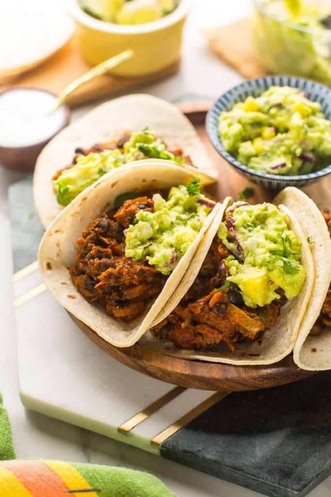 four Vegan Black Bean Tacos with Mango Guacamole on a plate