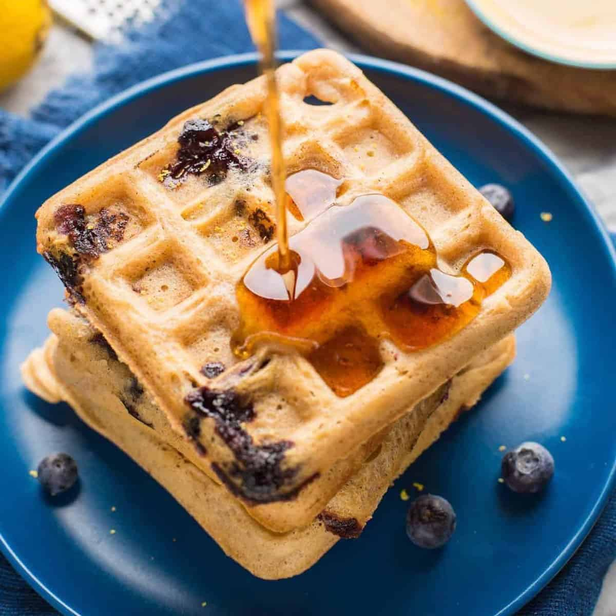 gluten free blueberry waffles with syrup pouring over the top