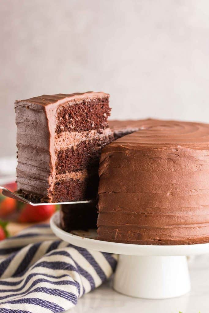 gluten free chocolate cake with a slice being picked up on a white cake stand