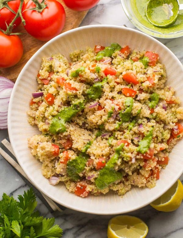 Tomato Quinoa Salad in a salad bowl surrounded by fresh veggies