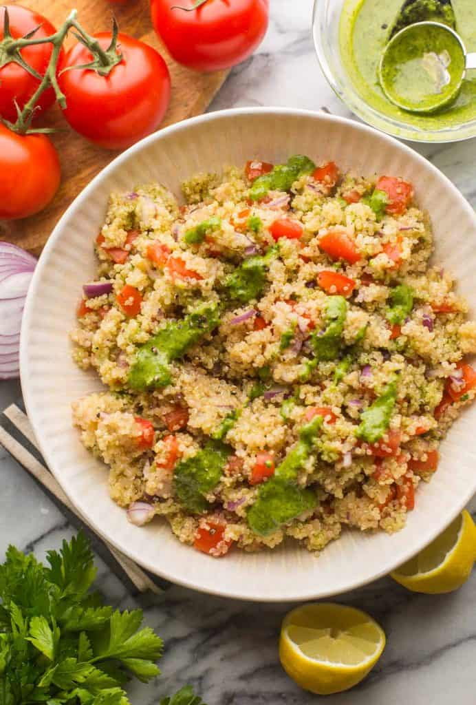 tomato quinoa salad in a bowl topped with zhoug dressing