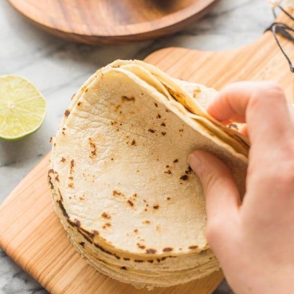 Homemade Corn Tortilla Recipe stack on a small cutting board